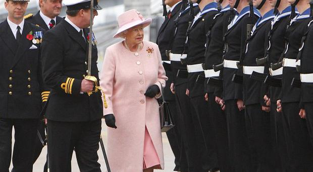 The Queen inspects the guard during a visit to HMS Ark Royal at the Royal Navy dockyard in Portsmouth