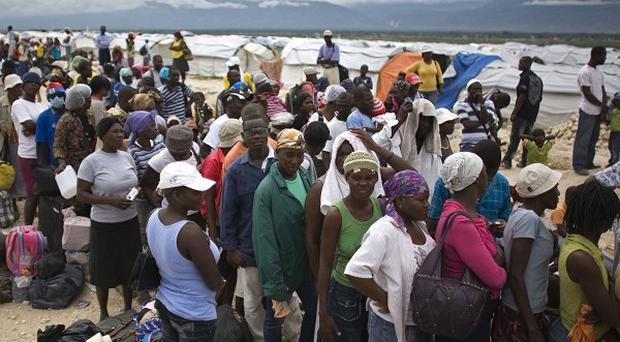 People wait to be evacuated from a Port-au-Prince refugee camp before the arrival of Hurricane Tomas