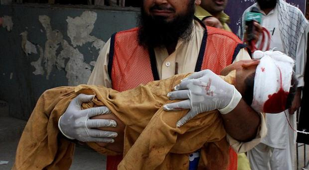A grief-stricken volunteer carries a child to a local hospital in Peshawar after a suicide bomber struck the mosque in Darra Adam Khel (AP)
