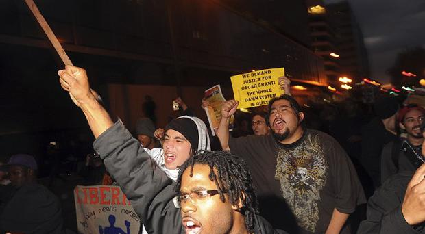 Demonstrators during street protests in reaction to the conviction of police officer Johannes Mehserle in Oakland, California (AP)