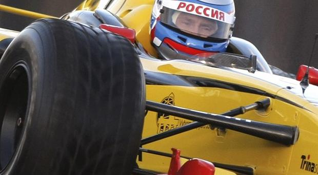 Russian prime minister Vladimir Putin drives a Renault racing car at a race track outside St Petersburg, Russia (AP)