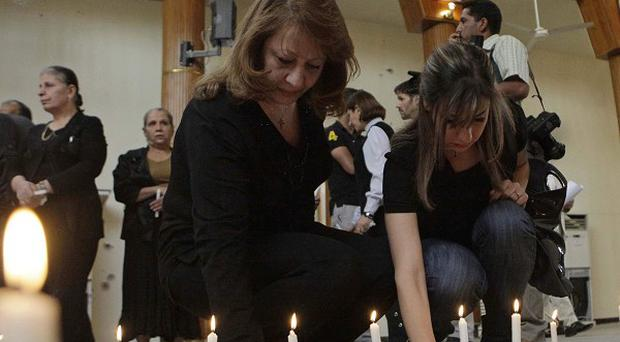 Christians light candles for the siege victims during a mass at Our Lady of Salvation church in Baghdad, Iraq (AP)