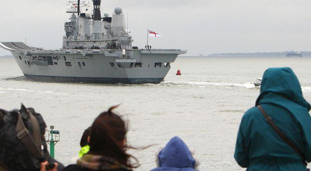 A crowd watches the Royal Navy flagship HMS Ark Royal leave Portsmouth for the last time