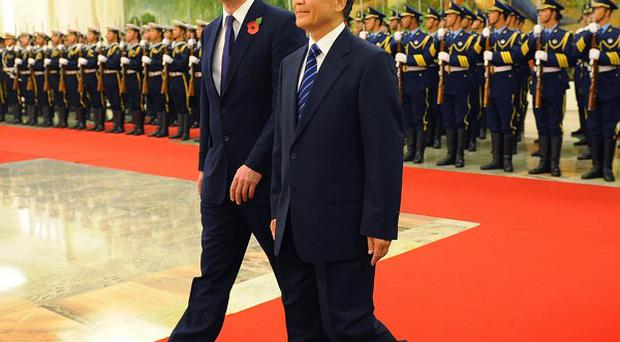 Prime Minister David Cameron inspects a guard of honour with Chinese premier Wen Jiabao