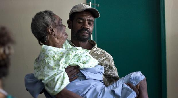 A woman suffering from cholera symptoms is carried by a volunteer at the hospital in Archaie, Haiti (AP)