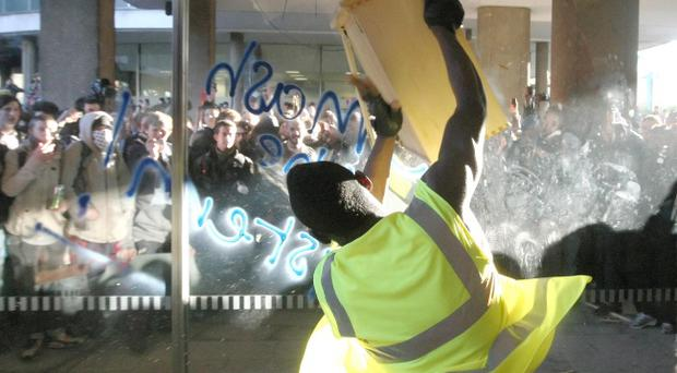 A demonstrator smashes the windows of Millbank Tower, in Westminster, central London as students and teachers gathered in central London to protest against university funding cuts and Government plans to charge up to £9,000 per year in fees from 2012.