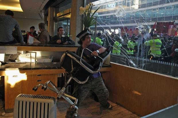 LONDON, ENGLAND - NOVEMBER 10: Student protesters smash windows as they clash with police after entering Millbank Tower home of Conservative Party headquaters on November 10, 2010 in London, England. Student groups are protesting against the government's proposed funding cuts to education and an increase in tuition fees. (Photo by Dan Kitwood/Getty Images)