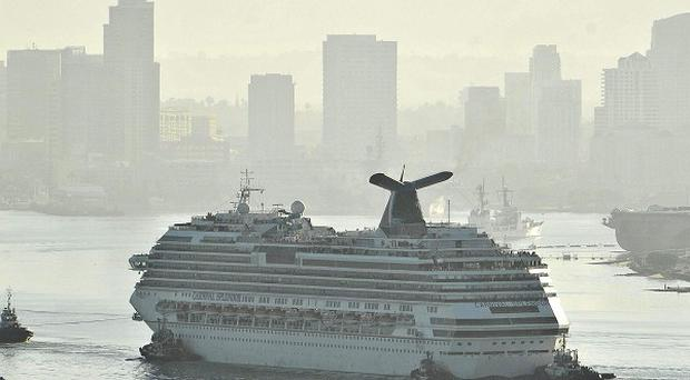 Tugboats tow the disabled cruise ship Carnival Splendor into San Diego Bay (AP)