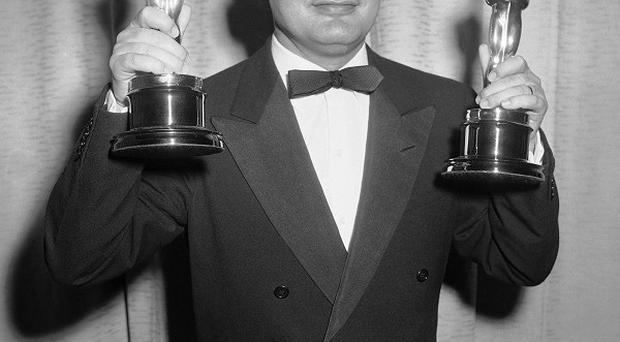 Dino De Laurentiis holds the Oscars awarded to him and Carlo Ponti in 1957 (AP)