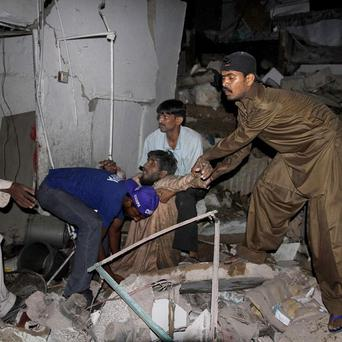 A Pakistan rescue worker and volunteers remove an injured person at the site of bomb explosion in Karachi