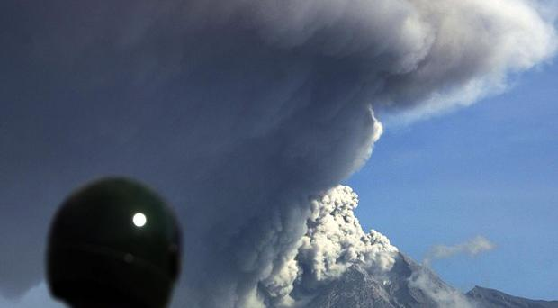 A man watches Mount Merapi spew volcanic material (AP)