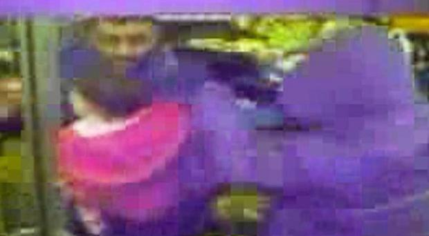A robber holds a gun to the head of a shopkeeper as he cradled his 15-month-old daughter in his arms