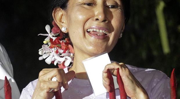 Aung San Suu Kyi talks to supporters at the gate of her home after being released from house arrest (AP)
