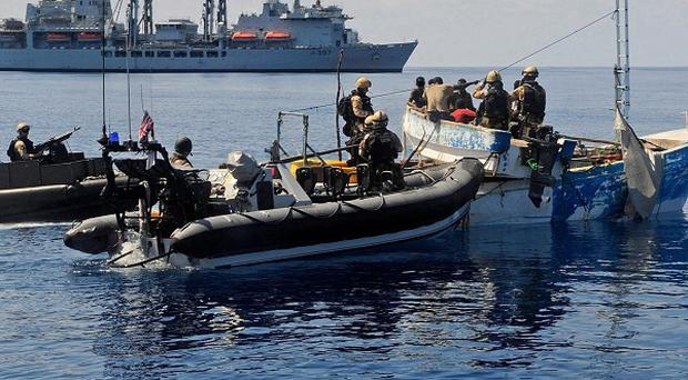 Troops on a Royal Marines raiding craft boarding and searching a Somalian Pirate Vessel