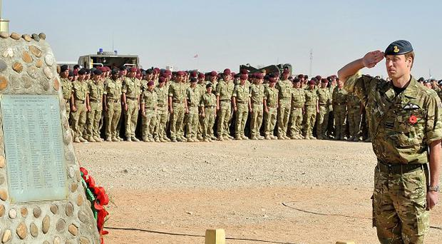 Prince William stands to attention and salutes the memorial to the British soliders killed in Afghanistan during a remembrance day ceremony at Camp Bastion