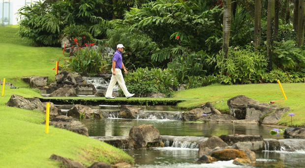 Graeme McDowell walks to the 16th green in the final round of the Barclays Singapore Open today