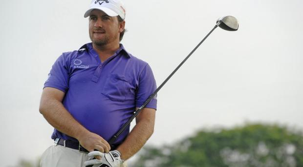 Graeme McDowell of Northern Ireland watches his tee-shot on the eleventh hole during round 4 of the Singapore Barclays Open golf tournament, Monday, Nov. 15, 2010, in Singapore.(AP Photo/Joseph Nair)
