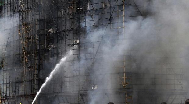People from another building watch firefighters extinguish a blaze in Shanghai (AP)