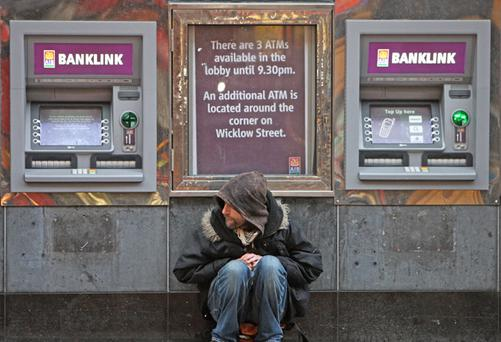 A man begs outside Anglo Irish Bank in Dublin's city centre