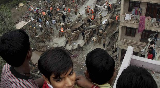 Local residents watch rescue workers search amid debris after a building collapsed in New Delhi (AP)