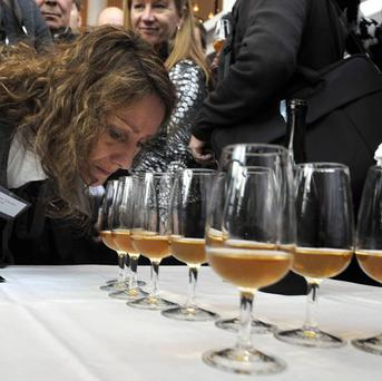 A woman smells the aroma of one of the 168 bottles of Champagne salvaged from a 200-year-old shipwreck