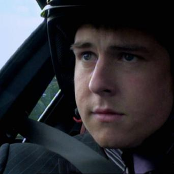 Stuart Baggs test drives a race car while the rest of his team are at work