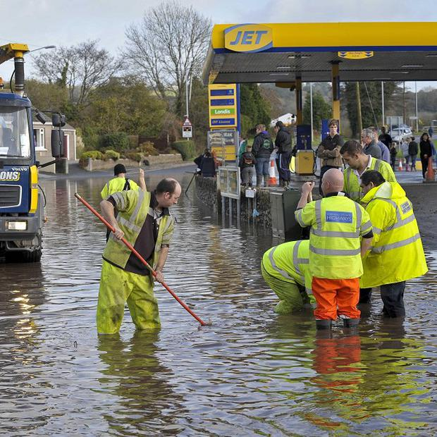 Workmen try to clear a drain in St Blazey, Cornwall, where flooding has closed off the village