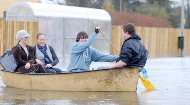 Local people using alternative transport to get through flooded roads at the Erneside Shopping centre on the edge of Upper Lough Erne. Nov 2010
