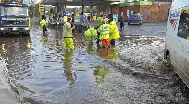 Workmen try to clear a drain in St Blazey, Cornwall where flooding caused havoc