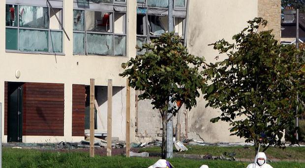 Forensics officers in Londonderry, after a car bomb exploded outside the Ulster Bank