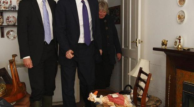Prime Minister David Cameron and local MP Steven Gilbert with Val Page in her flooded home in Cornwall