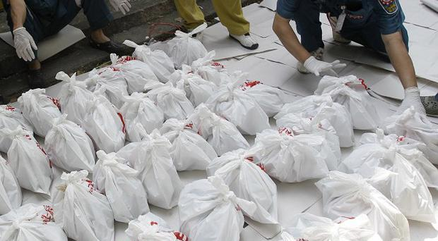 Rescue workers arrange bags containing dead foetuses found at the mortuary of a Buddhist temple in Bangkok