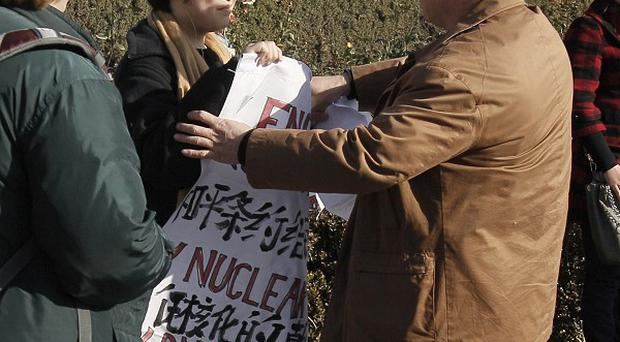 A plain clothes policeman, right, tries to stop Jonathan Lee outside the Forbidden City in Beijing, China (ASP)
