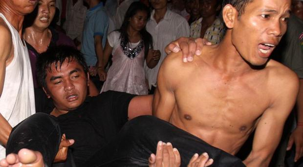 An injured Cambodian is carried away after a stampede onto a bridge in Phnom Penh (AP)