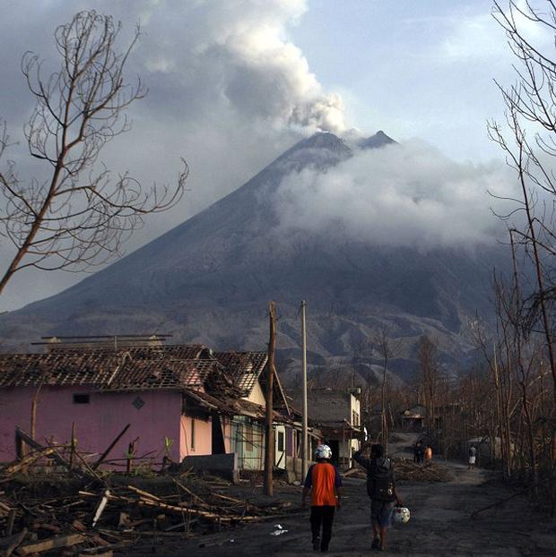 Villagers walk through destroyed houses in a village after the eruption of Mount Merapi at Umbulharjo in Cangkringan, Indonesia (AP)