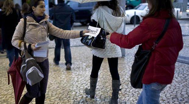 A woman hands out leaflets callilng for a general strike to commuters in Lisbon (AP)