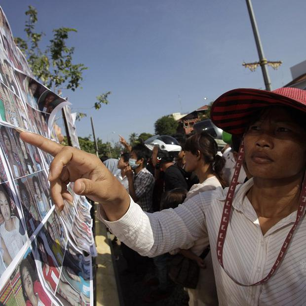 A Cambodian woman views photos of stampede victims at Preah Kossamak Hospital in Phnom Penh (AP)