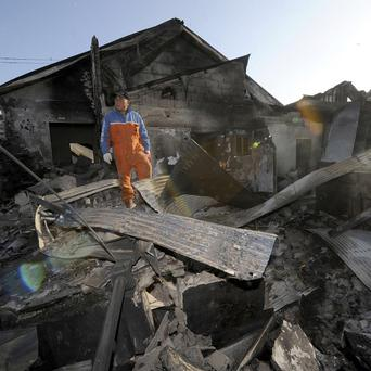 A South Korean resident stands on the rubble of a destroyed house on Yeonpyeong island (AP)