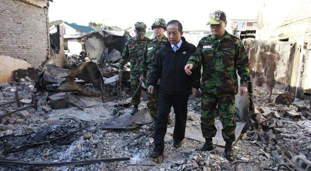 South Korean Defense Minister Kim Tae-young, center, looks at the destroyed houses on Yeonpyeong Island, South Korea, Thursday, Nov. 25, 2010