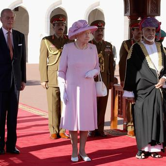 The Queen, Duke of Edinburgh and Sultan Qaboos bin Said take the salute during a visit to Al-Alam Palace in Muscat, Oman