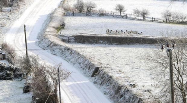 A motorist carefully driving on the icy roads on the hills outside Doagh, County Antrim
