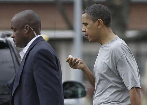President Barack Obama walks with a U.S. Secret Service agent back to his vehicle after playing a private game of basketball at Fort McNair in Washington, Friday, Nov. 26, 2010