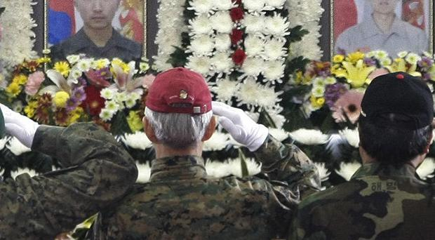 Marine veterans salute in front of the portraits of two killed South Korean marines during a funeral service (AP)