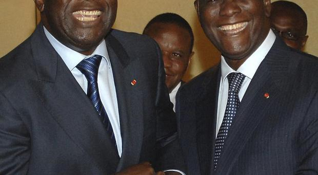 Ivory Coast president Laurent Gbagbo, left, and opposition presidential candidate Alassane Ouattara pose together for photographers (AP)