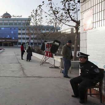 A policeman guards the entrance to the north west China school where dozens of children were hurt in a stampede (AP)