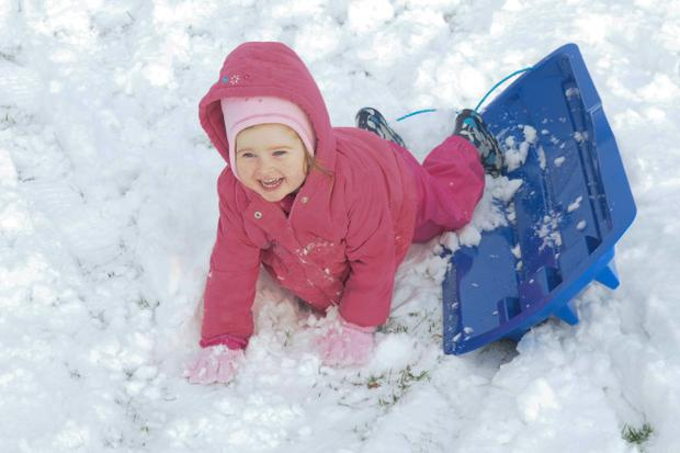 Two-year-old Sophie Duffy enjoys herself after falling out of her sleigh at LIsnagelvin in Derry