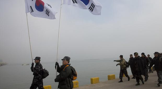 South Korean military veterans arrive at the port at South Korea's Yeonpyeong Island. China has said it would accept a united Korea, according to WikiLeaks (AP)