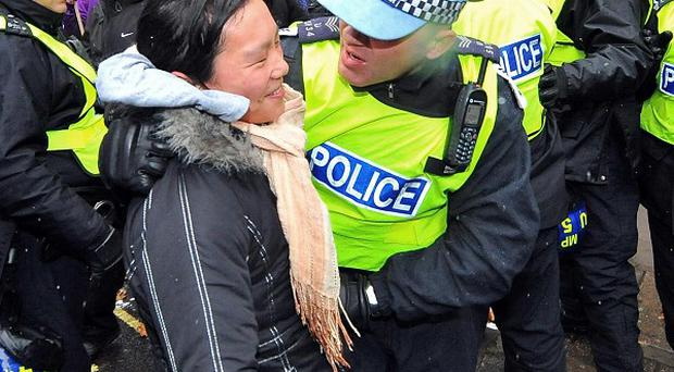 A protester scuffles with police officers during a march by students against university fees