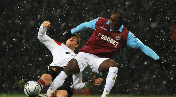 Carlton Cole of West Ham United challenges Jonny Evans of Manchester United during the Carling Cup Quarter Final match between West Ham United and Manchester United at the Boleyn Ground on November 30, 2010.