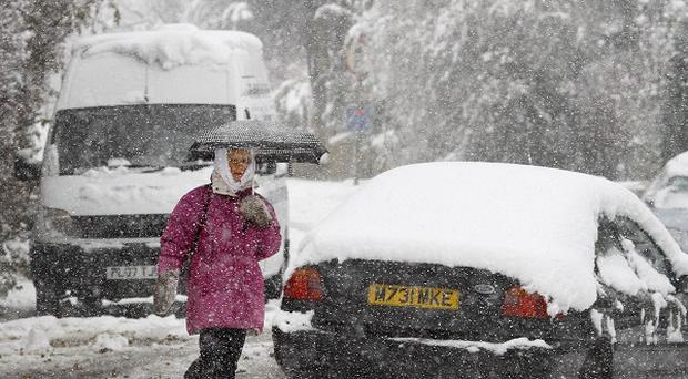 A woman braves the snow near Farningham, Kent